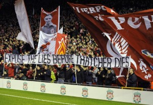 Liverpool fans hold up banners before their English League Cup semi-final soccer match against Manchester City at Anfield in Liverpool