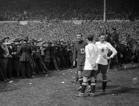 28th April 1923: West Ham United and Bolton Wanderers players wait for the police to clear the pitch of spectators and allow the FA Cup final to kick off after a 45 minute delay. The newly completed Wembley stadium is host to the FA Cup final for the first time and although the stadium's capacity is said to be 127,000 the match is massively over attended and police allow fans to watch from the sidelines. (Photo by Topical Press Agency/Getty Images)